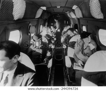 Stylishly dressed passengers seated in a commercial flight in the 1930s. Stok fotoğraf ©