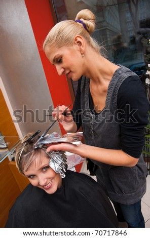 stylist coloring woman hair in hairdresser salon