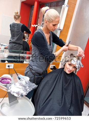 stylist coloring woman hair in salon