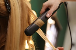 Stylist curling woman's hair with flat iron in salon, closeup