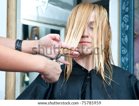 stylist cutting woman hair and making new hairstyle in salon