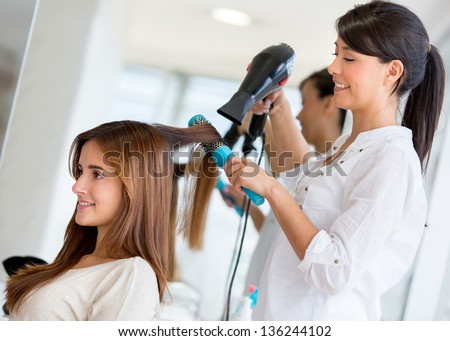 Stylist drying hair of a female client at the beauty salon