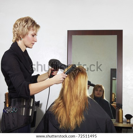 stylist drying woman hair in beauty salon