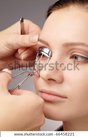 Stylist is forming eyelashes using curler for young girl