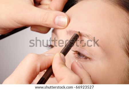 Stylist is penciling eyebrow for young girl - stock photo