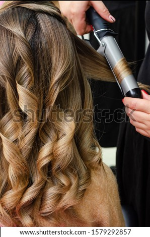 Stylist making a hairdo with hair curler. Beauty salon concept. Vertical