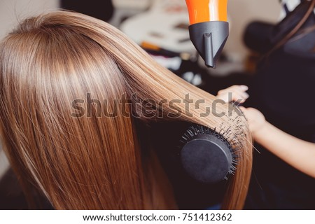 Stylist puts hair dryer and comb in hairdresser