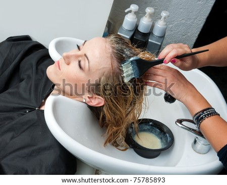 stylist putting color on woman hair in salon pool