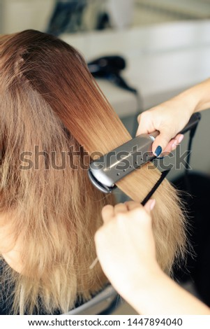 stylist's work with the hair of a girl in a beauty salon #1447894040