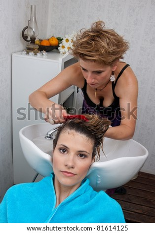 stylist washing and combing attractive woman hair in salon pool
