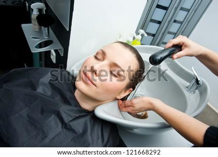 stylist washing attractive woman hair in salon