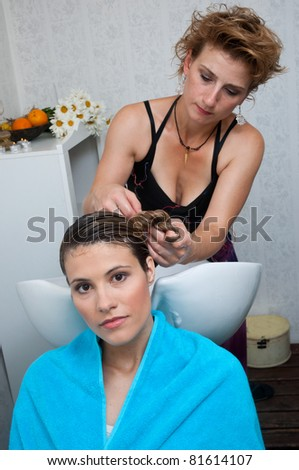stylist washing attractive woman hair in salon - stock photo