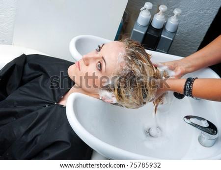 stylist washing woman hair in hairsalon