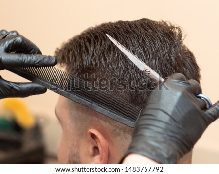 Stylist working with clients hairdress, close up view. Master cutting hair with scissors and comb. Stylist at work in hairdressing saloon. Selective soft focus. Blurred background