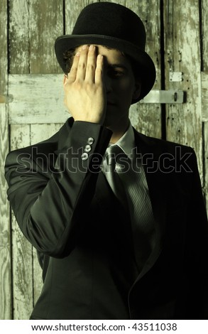 Stylized abstract portrait of a dapper man in top hat and suit covering half of his face with hand - photo has a slight green toned effect