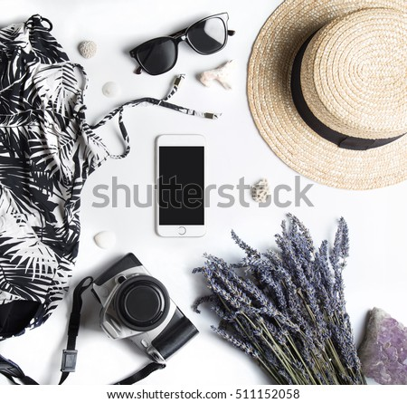 Stylized feminine flatlay with swimming suit, sunglasses, camera, hat, bunch of lavender, crystal stone, sea shells and smart phone mock up isolated on white top view. Woman accessories from above.