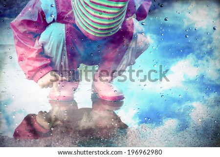 stylized photo of  cute little girl is playing in muddy puddles