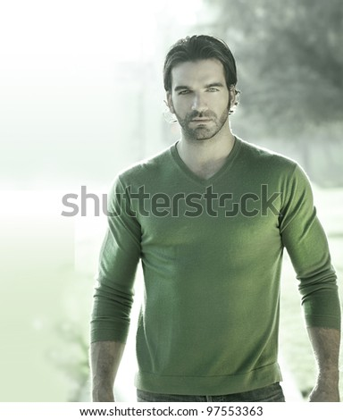 Stylized portrait of a great looking masculine guy outdoors in green sweater