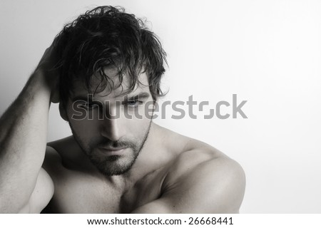 Stylized portrait of masculine attractive young shirtless man with beard against white background
