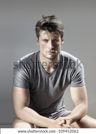 Stylized portrait of masculine handsome young man against neutral background
