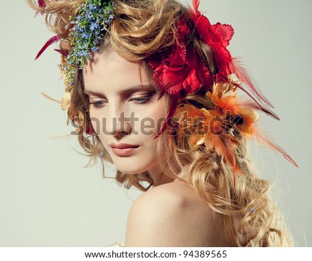 Stylized summer portrait of a young beautiful woman with flowers in her hair