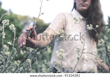 Stylized vintage shoot of a young woman in a field of wild flowers, deliberately edited in a cooler colour tone