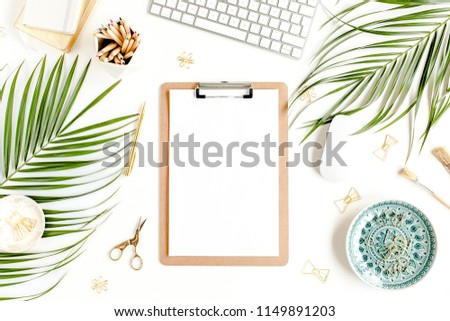 Stylized women's desk. Workspace with clipboard, tropical palm leaves, computer, accessories on white background. Flat lay. Top view.