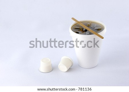 Styrofoam coffee cup with two creamers.