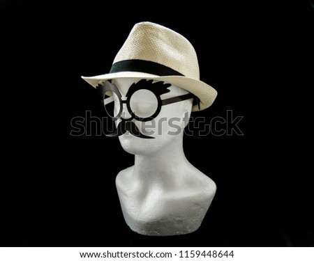 Styrofoam head with a straw male summer hat and glasses with moustache on black background left side