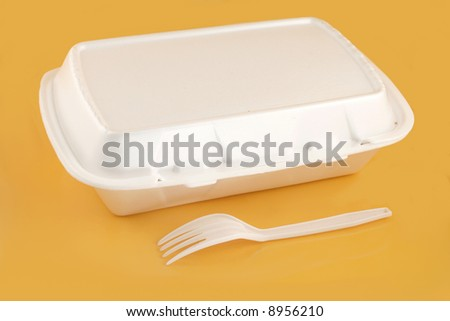 styrofoam take-out food container and plastic fork on a yellow background