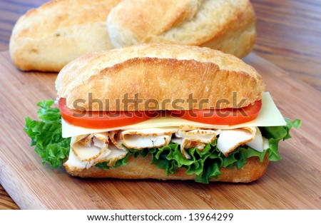 Sub sandwich of turkey, tomatoes, lettuce and cheese on a cutting board with loaves of bread behind.