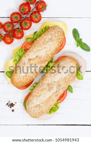 Sub sandwich whole grain grains baguette with cheese and ham from above portrait format on wooden board wood