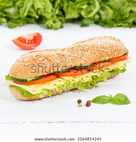 Sub sandwich whole grain grains baguette with cheese square on wooden board wood #1064814245