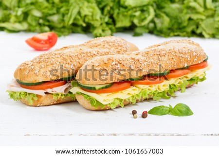 Sub sandwiches whole grain grains baguettes with ham and cheese on wooden board wood #1061657003