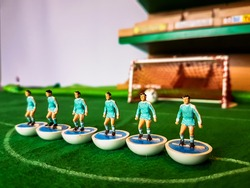 Subbuteo football figures lined up on a grass football field, Manchester City