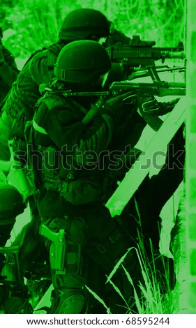 Subdivision anti-terrorist police during a black tactical exercises. Entry to the premises. Real situation. View through the night vision device. - stock photo