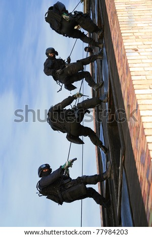 Subdivision anti-terrorist police during a black tactical exercises. Officer in full tactical gear with weapons climbing down a rope. Rope Techniques.  Real situation.