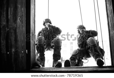 Subdivision anti-terrorist police during a black tactical exercises. Rope Techniques.  Real situation. Black and white photo with film grain.