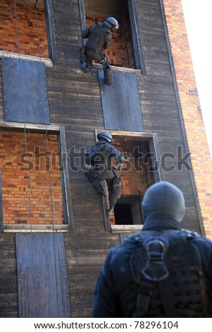 Subdivision anti-terrorist police during a black tactical exercises. Rope Techniques wih instructor.  Real situation.