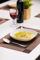 Subject photo of served dinner table with white plate of meal on rectangle brown and beige woven placemat. Spoon, fork, wine bottle, glass with ruby drink and pot flowers are located on the table.