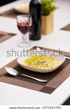 Subject photo of served dinner table with white plate of meal on rectangle brown and beige woven placemat. Spoon, fork, wine bottle, glass with ruby drink and pot flowers are located on the table.  Stock photo ©