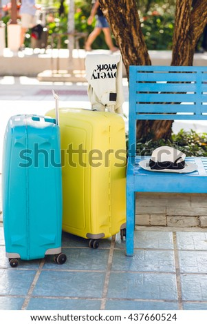 Subject photo of two suitcases - blue and yellow standing near blue bench in a park. A white sweater is hanging on a handle of yellow suitcase. There is a straw hat lying on a bench.