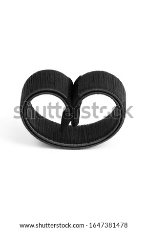 Subject shot of a black hairdo-shaper hairagami. The rolled hair-bun maker is isolated on the white background.