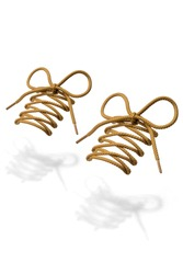 Subject shot of mustard shoe strings with thin tips. The plaited shoe laces are tied in a bow and hanging in the air on the white background.