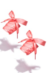 Subject shot of pink shoe strings made of silk ribbon. The shoe laces with thin tips are tied in a bow and hanging in the air on the white background.