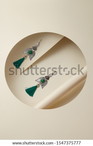 Subject shot of silver hook earrings with a tracery wings-shaped pendant with beads, crystals and a green thread tassels. The earrings are isolated on the ivory white surface with geometric design.  #1547375777