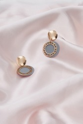 Subject shot of two earrings with pendants. Each earring is made as curved golden disc with hanging gray plate with fretted golden rim. The pair of earrings is located on the pink silk cloth.