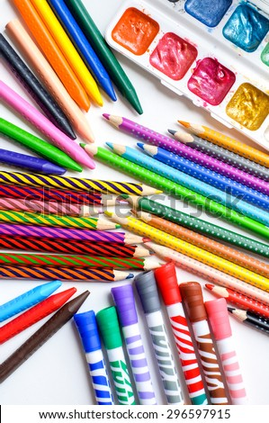 Subjects for drawing. Colored pencils, crayons, markers and paints on white background