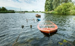 Submerged orange rowing boat near the banks of river.