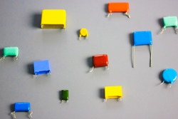 Subminiature polypropylene multicolored film capacitors on gray background flatly. Vintage electronic parts. Resistors and capacitors different size and color. HiFi Audio parts. Radio components.